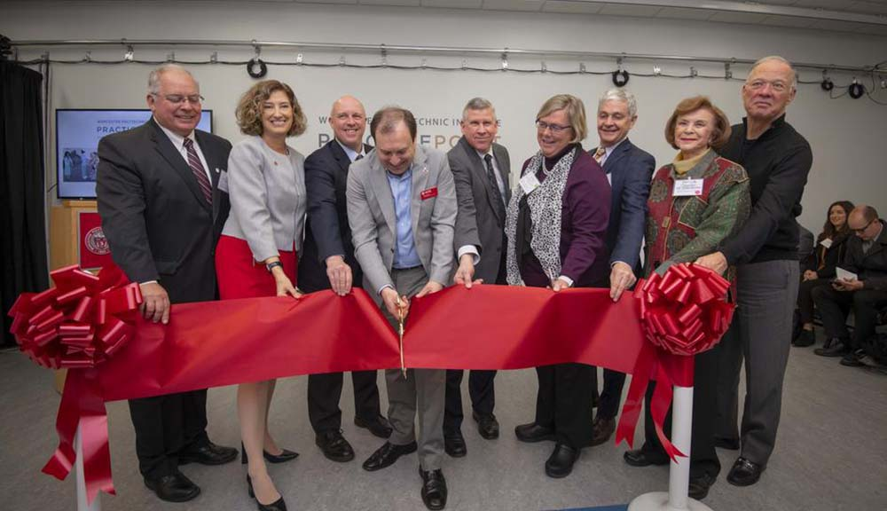 A large group including Laurie Leshin and Greg Fischer hold up a red ribbon as Fischer cuts it with gold scissors, symbolizing the grand opening of PracticePoint.
