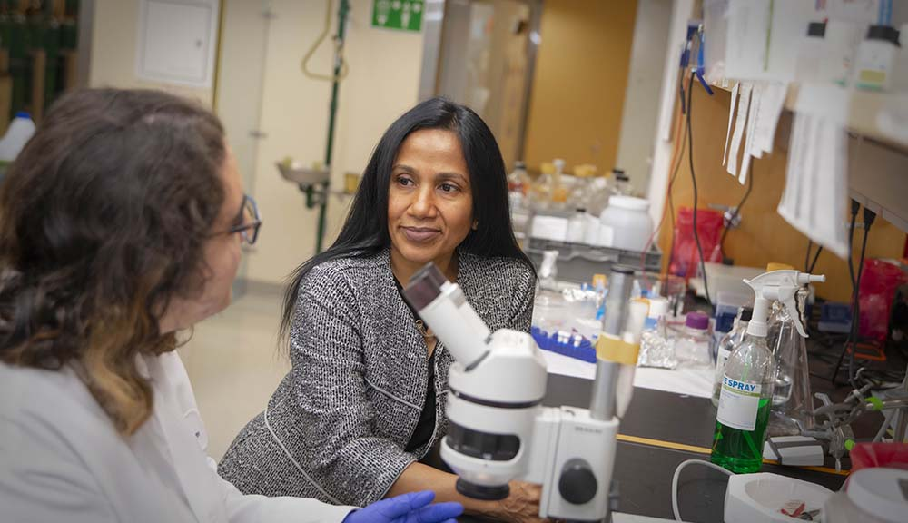 Reeta Rao discusses a subject with a student in the lab in front of science equipment.
