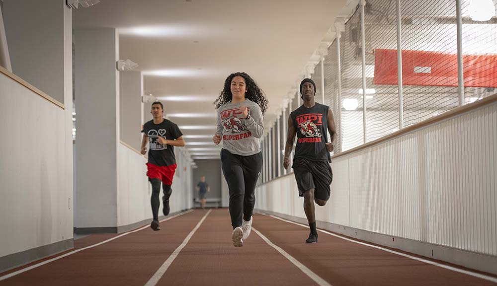 Three WPI students run in each lane of the indoor track in the Sports & Recreation Center.