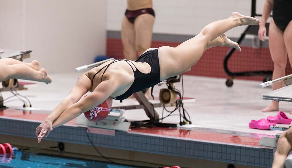 A member of the WPI women's swimming and diving team prepares to dive into the pool during a meet.