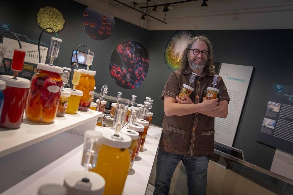 Professor Joshua Rosenstock, standing in his Fermentophone exhibit at the Harvard Museum of Natural History.
