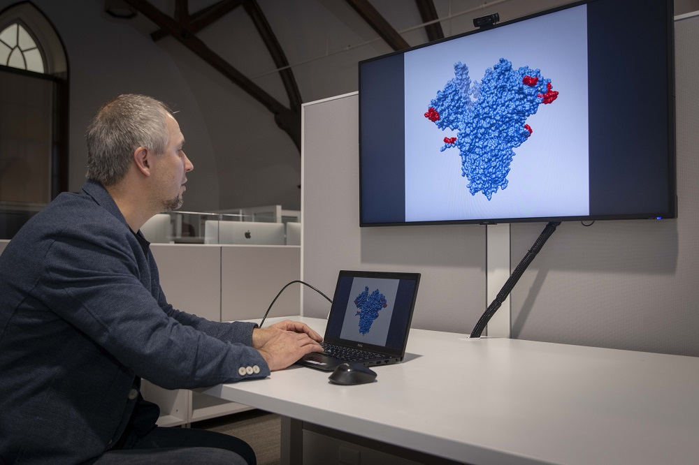 WPI bioinformatics researcher Dmitry Korkin examines a 3D model of a key protein of the novel coronavirus.