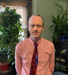 This is a photo of a man wearing an orange button up shirt with a tie. There is a plant in th ebackground