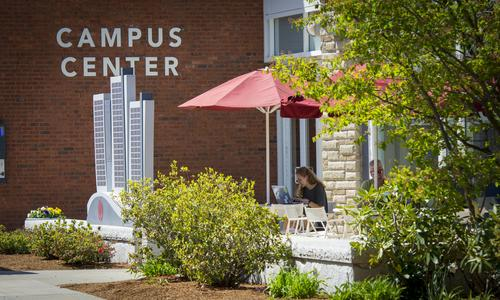 female student studying at campus center patio