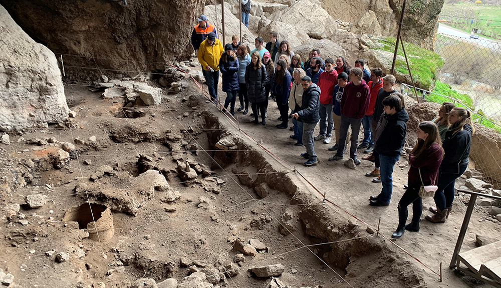 Archeologist Boris Gasparyan (center) guides a tour of WPI project students at the Areni Cave excavation site in Armenia, dating back 6,000 years, where the first evidence of wine making was discovered.