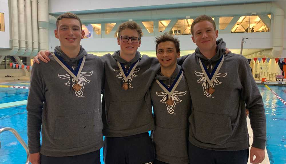 Members of the men's swimming and diving team smile for a photo while wearing their WPI sweatshirts and medals.