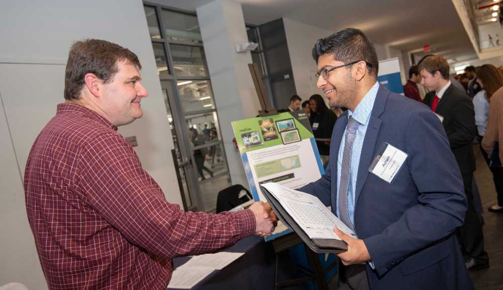 An employer attending the Spring Career Fair shakes hands with a WPI student.