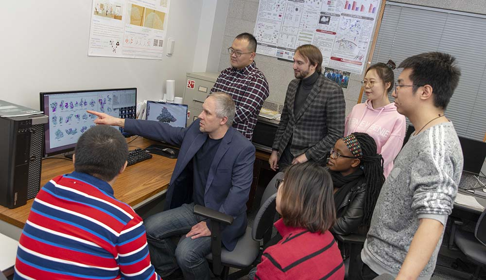 Dmitry Korkin gestures toward a computer screen with his team looking on at their work on display.
