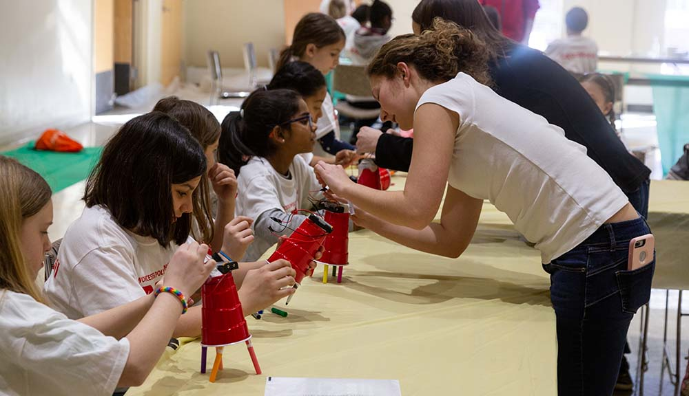 A WPI student helps elementary schoolers with a project during an Engineers Week activity.