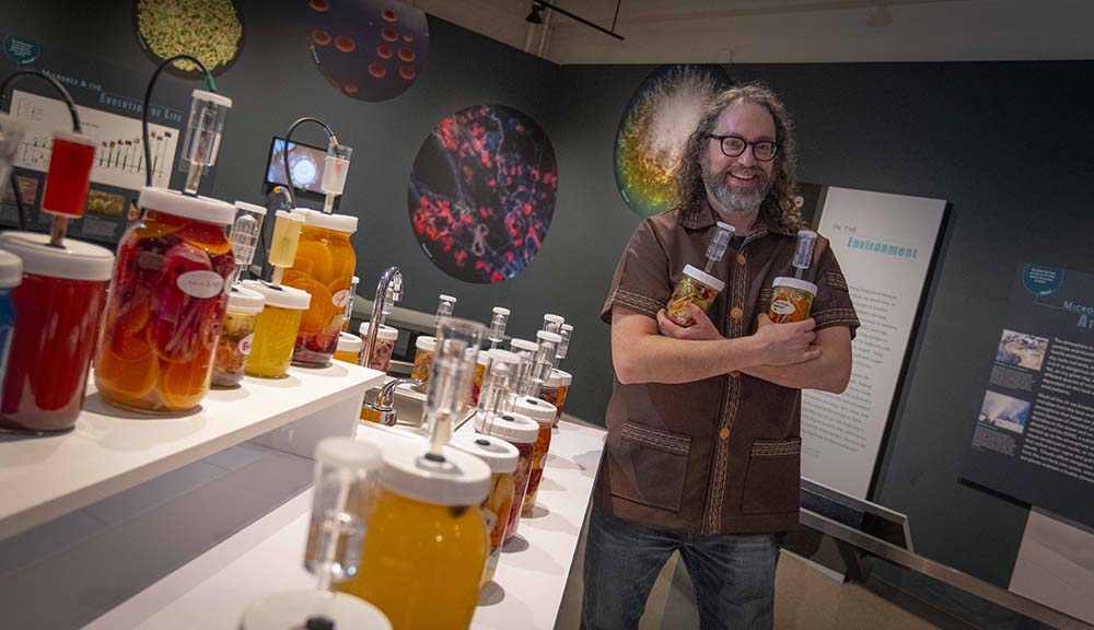 Joshua Rosenstock smiles for the camera with his jars of fermented fruits and vegetables on hand.
