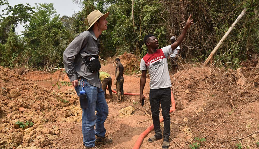 A WPI student discusses the specifics of an outdoor project with a Ghanaian resident.