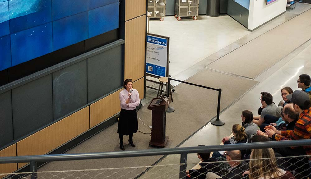 Taylor Rees addresses a crowd in front of the screen at the Foisie Innovation Studio.
