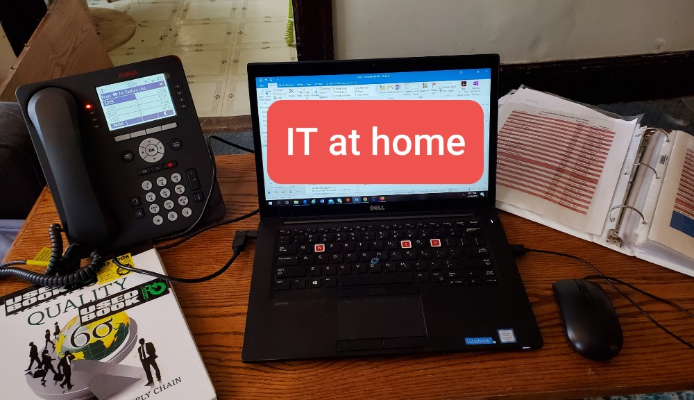 "A laptop with a red block that reads ""IT at home"" is sitting on a desk next to a telephone and a workbook."