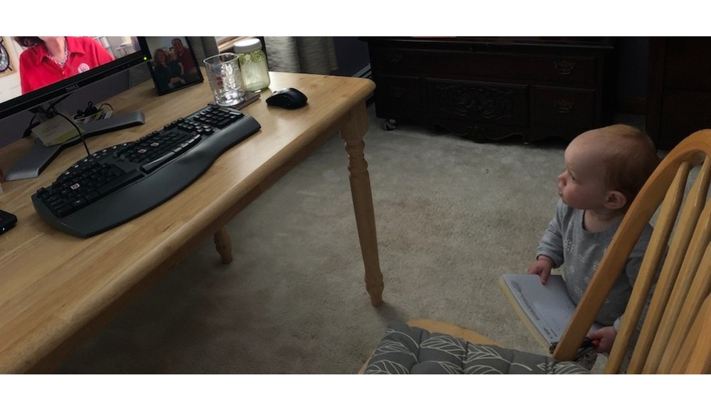 A toddler looks up at a computer screen while holding a notebook in her hands.