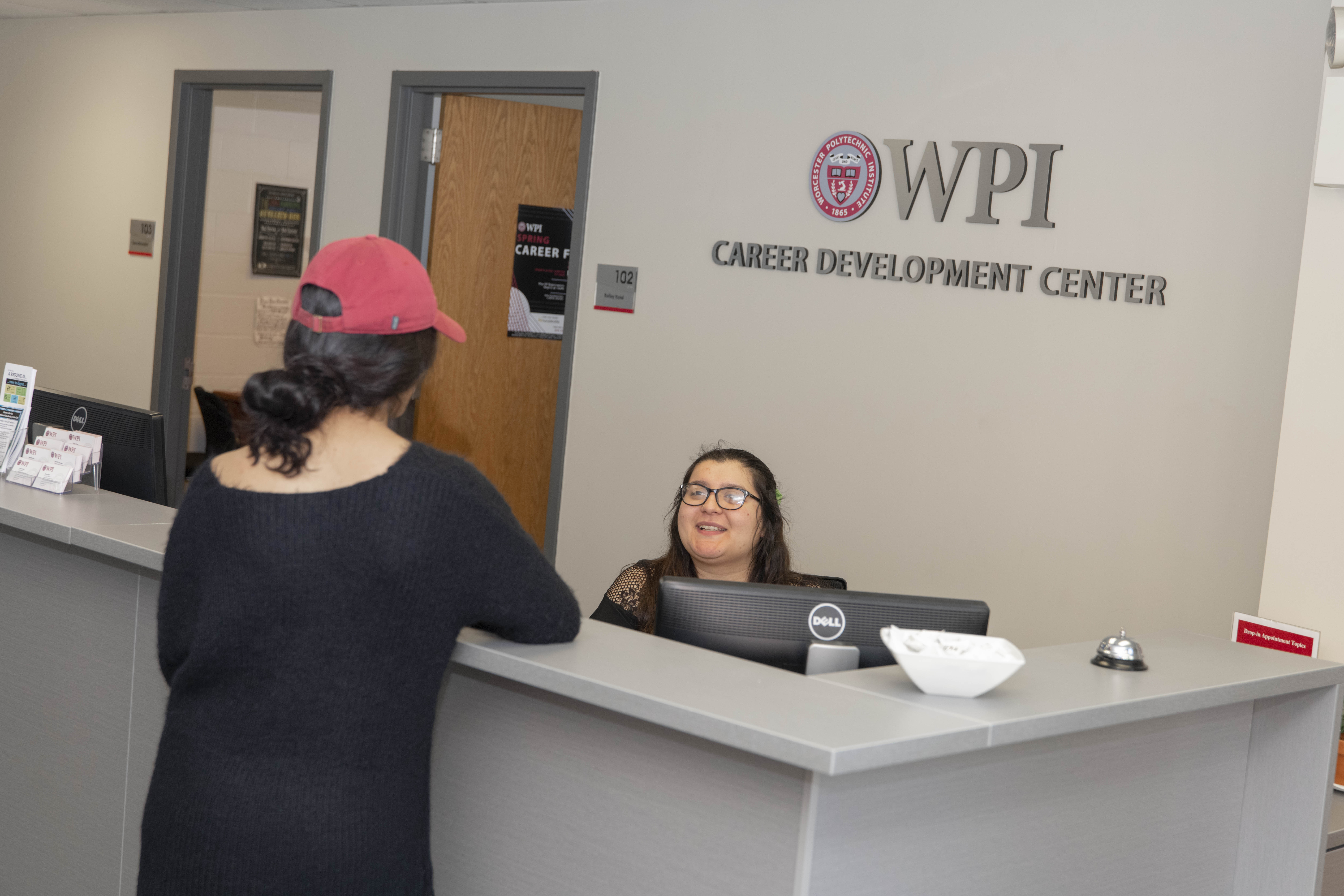 Picture of a student talking to the Career Development Center's student worker at the front desk of the Career Development Center.