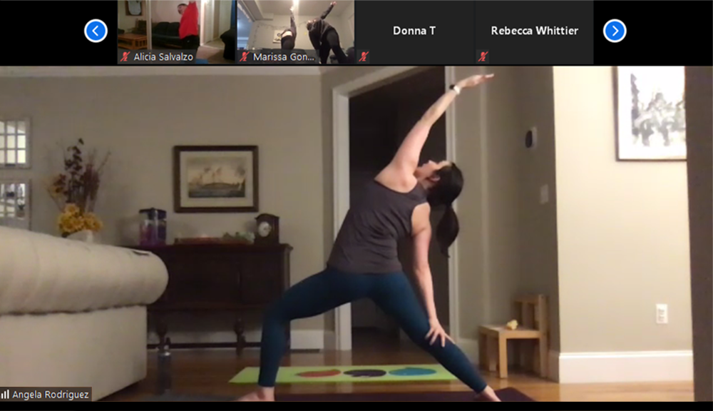 Angela Rodriguez, assistant professor of psychology, guides her yoga class into a Reverse Warrior pose.