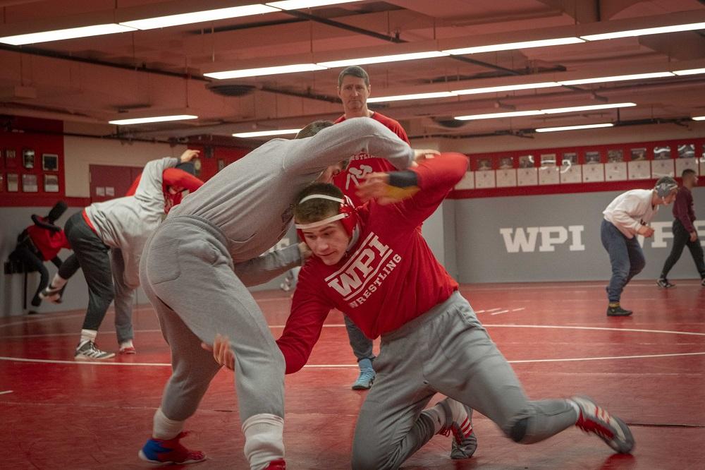 WPI wrestler Tyler Marsh practices a move under the watchful eye of Coach Matt Oney.