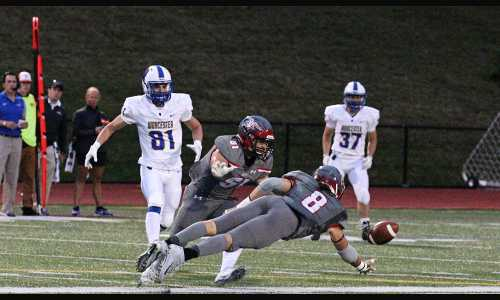 Sam Casey, wearing a gray uniform with the number eight, dives for the football during a night game at Alumni Stadium.