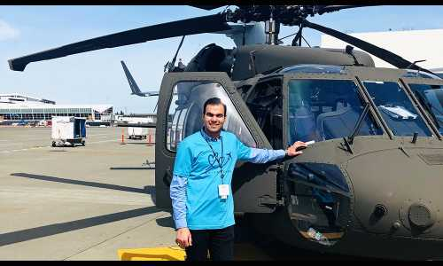 Abdullah Hussein Al-Shawk smiles for a photo while standing next to a dark green helicopter. He's got his hand on the helicopter and is wearing a bright blue shirt.