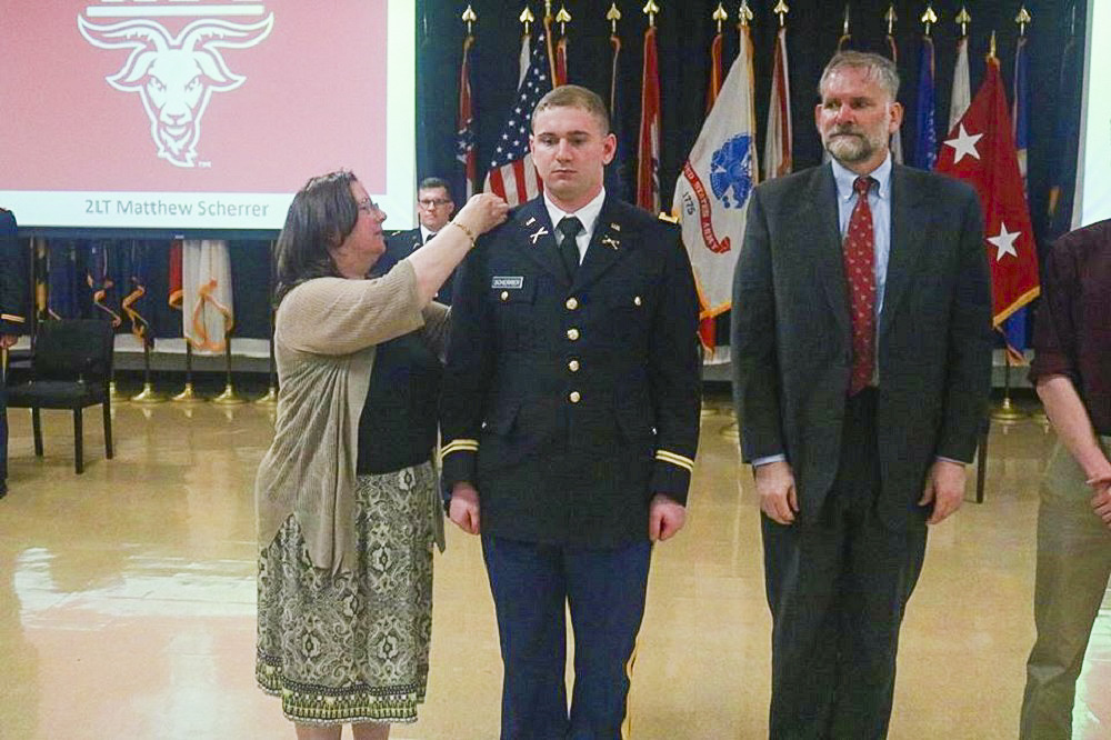 Army 2nd Lt. Matthew Sherrer of Wellesley has his gold bars pinned on by his parents, Janet and Stephen Sherrer.