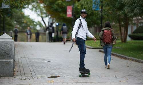 A student rides a skateboard across campus.