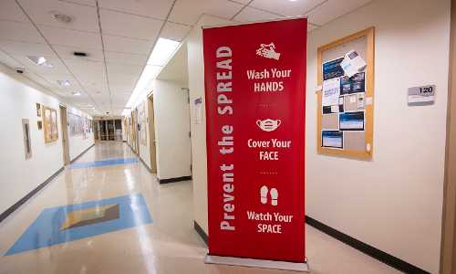 A photo of a red banner in a WPI hallway with new signage related to COVID-19 rules and procedures. alt