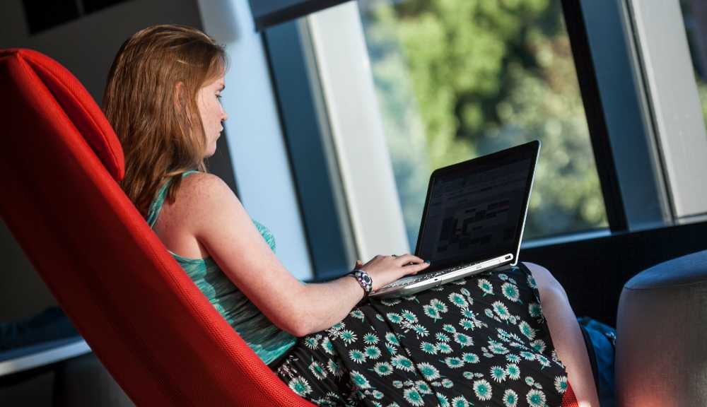 A student works on her laptop in a red chair at the Foisie Innovation Studio.
