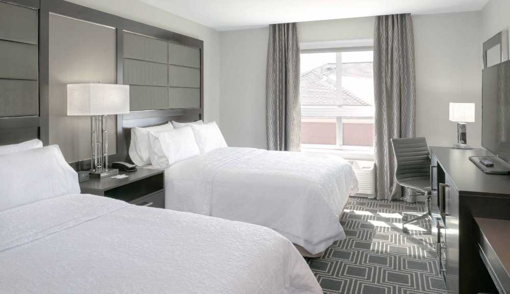 A photo of two beds with white linens in the Hampton Inn hotel.