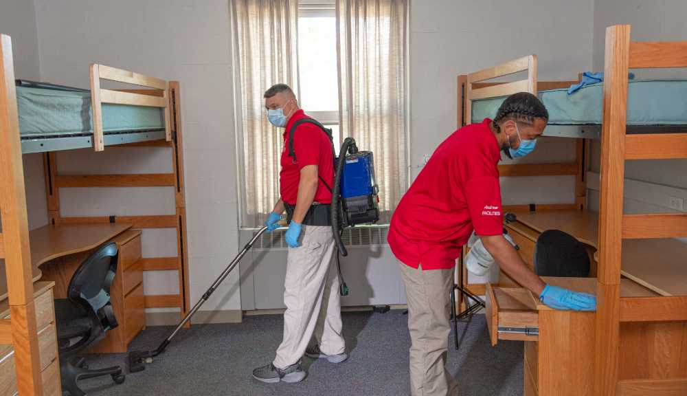 Two custodians wearing PPE work to clean a student residence.