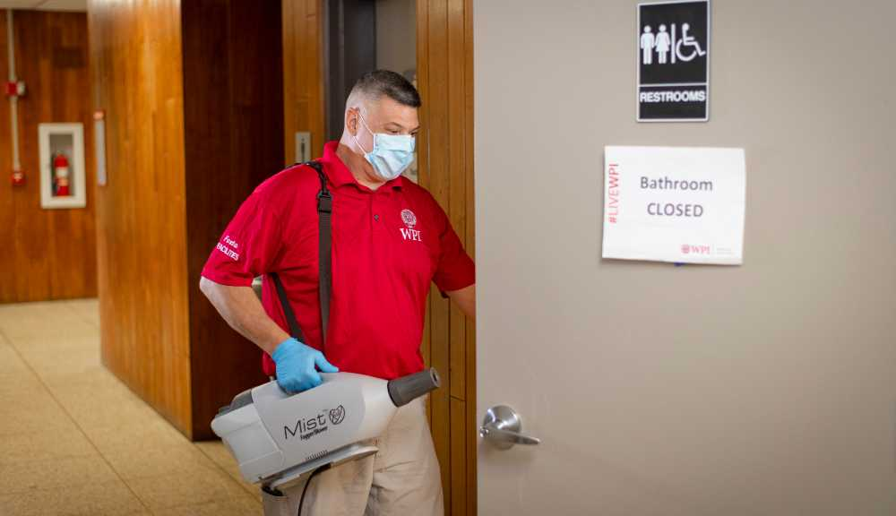 A custodian wearing PPE enters a restroom to begin the cleaning process.