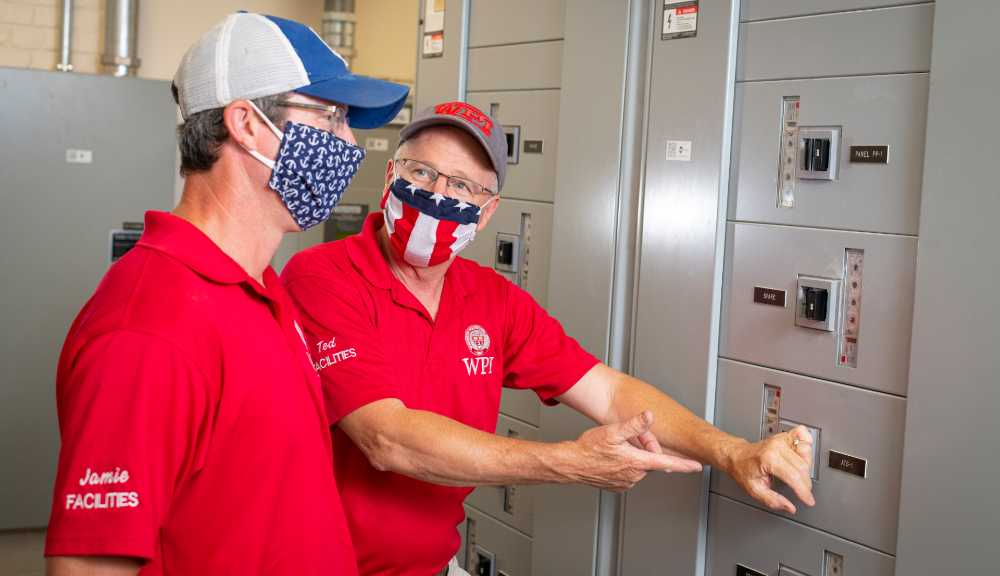 Two electricians wearing face coverings talk together while one gestures to some electrical equipment.