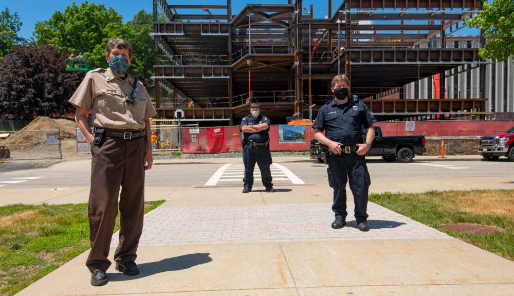 Three officers stand socially distanced from each other while wearing face coverings. The frame of the new Boynton Street building stands in the background.
