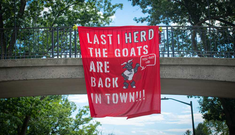 "A red banner reading ""Last I heard the goats are back in town!!!"" hanging from Earle Bridge."