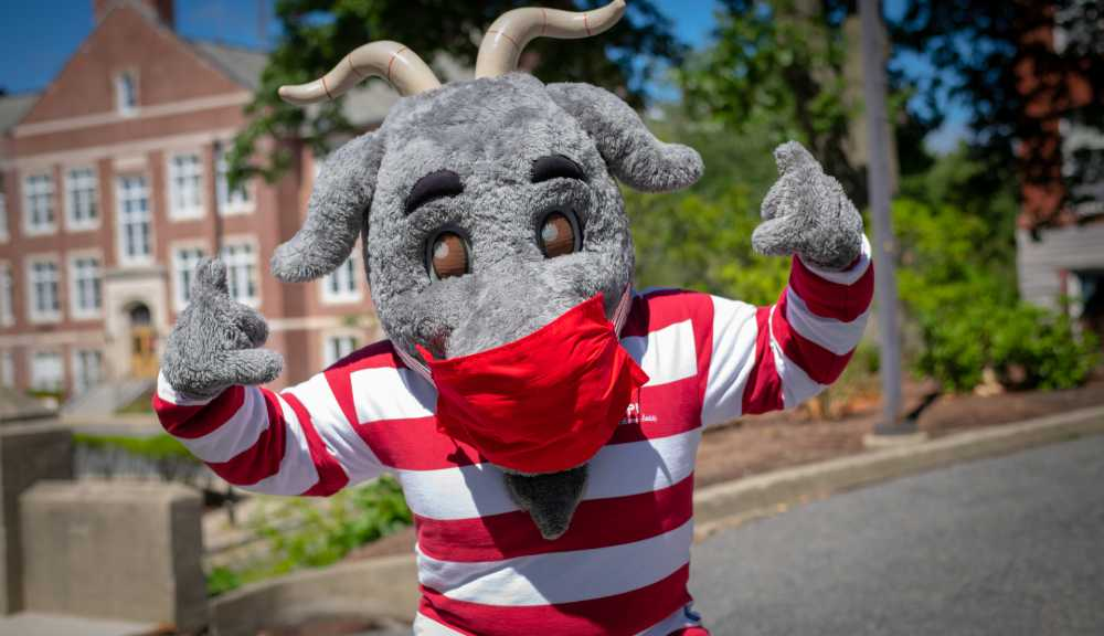 Gompei the Goat wears a red and white striped shirt and a red mask while flashing thumbs up.