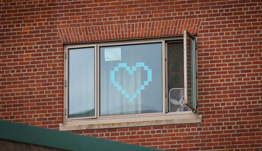 A heart made out of blue sticky notes designed on the window of a residence.