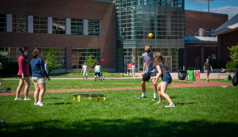 A small group of four students play a socially-distanced game of spikeball on the Quad.