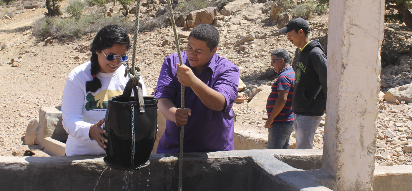 Students working together to pull a bucket of water up from a well