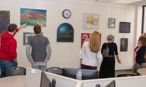 Students looking at art on a wall during Arts & Sciences Week