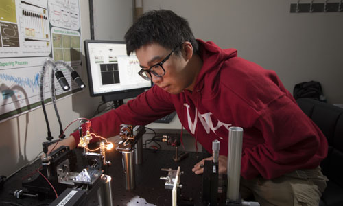 Student in a red WPI sweatshirt doing a research experiment