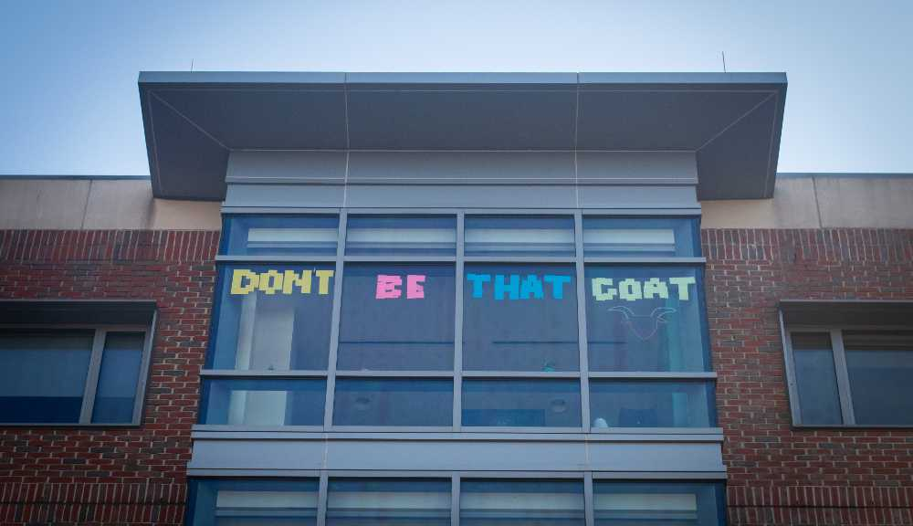 "Sticky notes arranged across several windows to spell out ""Don't Be That Goat."""