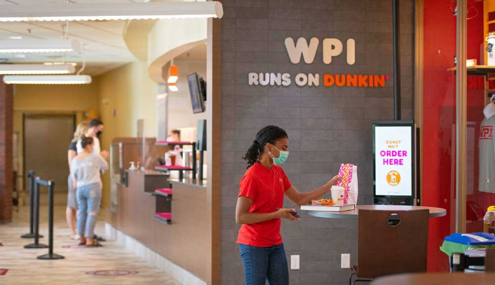 A student picks up a Dunkin' order in the campus center.