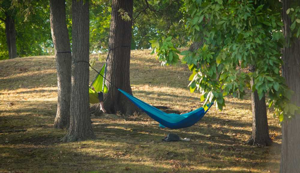 Students lounge in hammocks on campus.