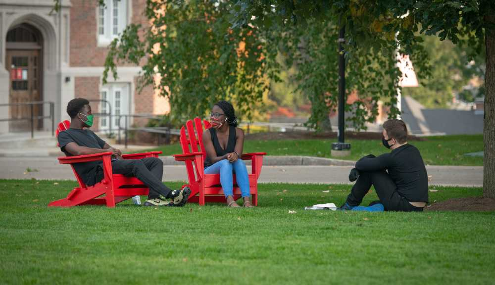 Students relax in Adirondack chairs on campus.