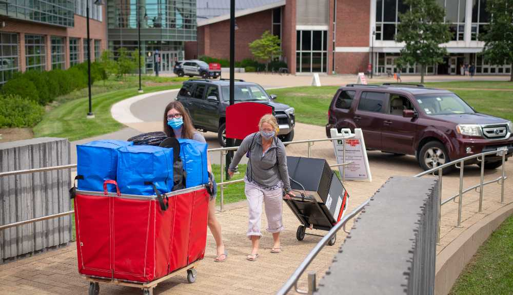 A student and parent push a red bin and pull a dolly with a mini fridge secured to it to a WPI residence hall.