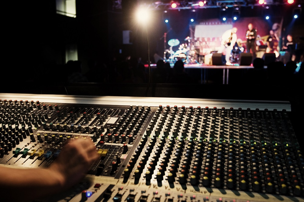 A person works a soundboard while musicians play.