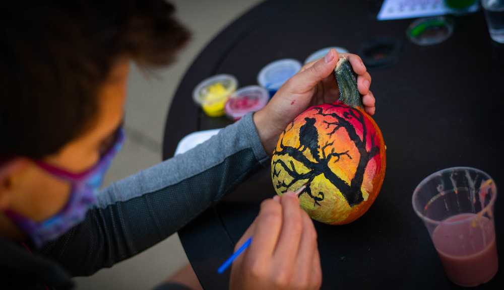 An over-the-shoulder shot of a student painting a pumpkin.