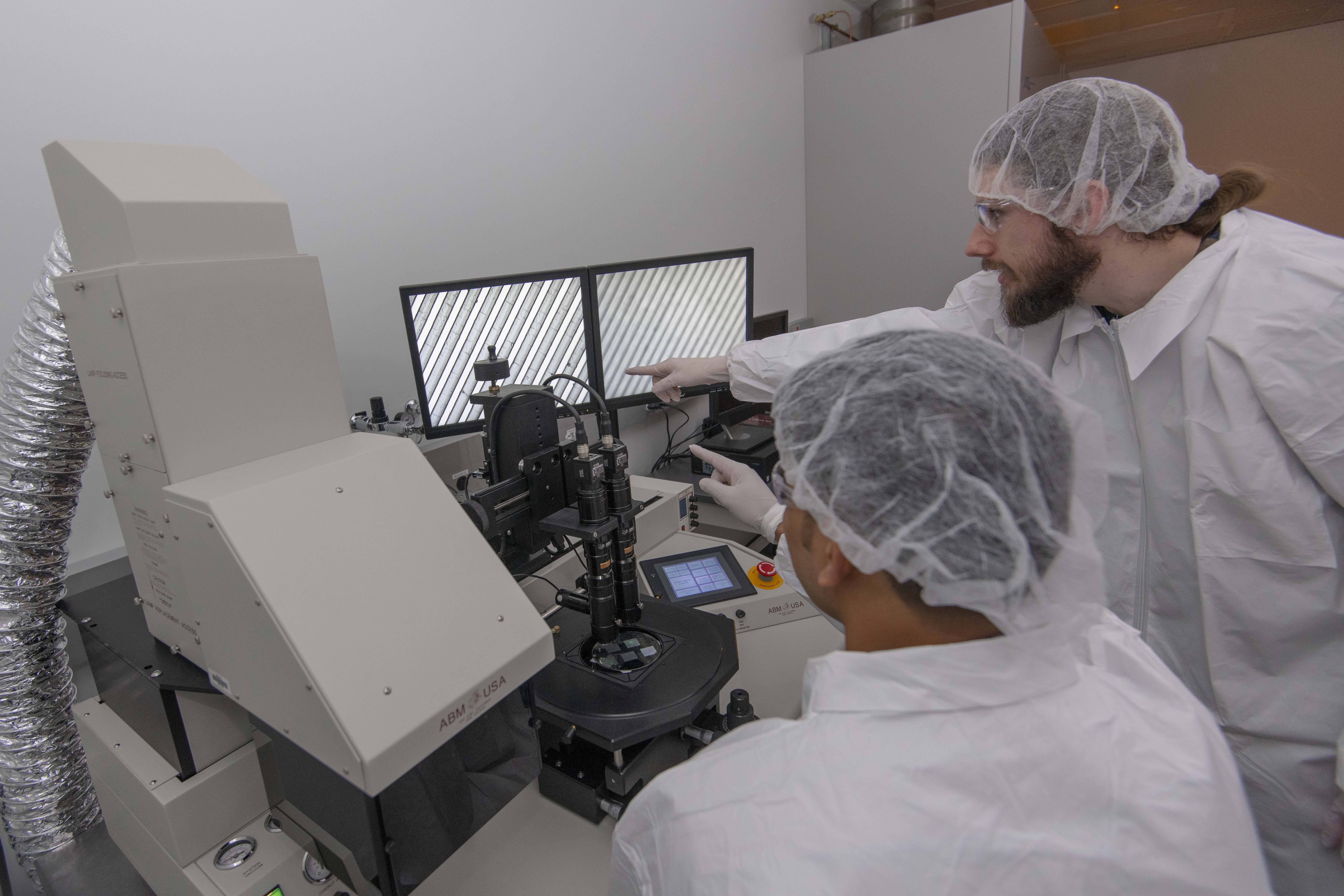 Image of graduate students working at a lab station alt