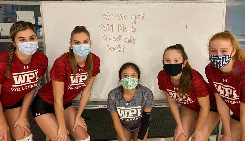 """A photo of members of the women's volleyball team pose in front of a whiteboard that says """"We've got WPI men's basketball's back!"""""""