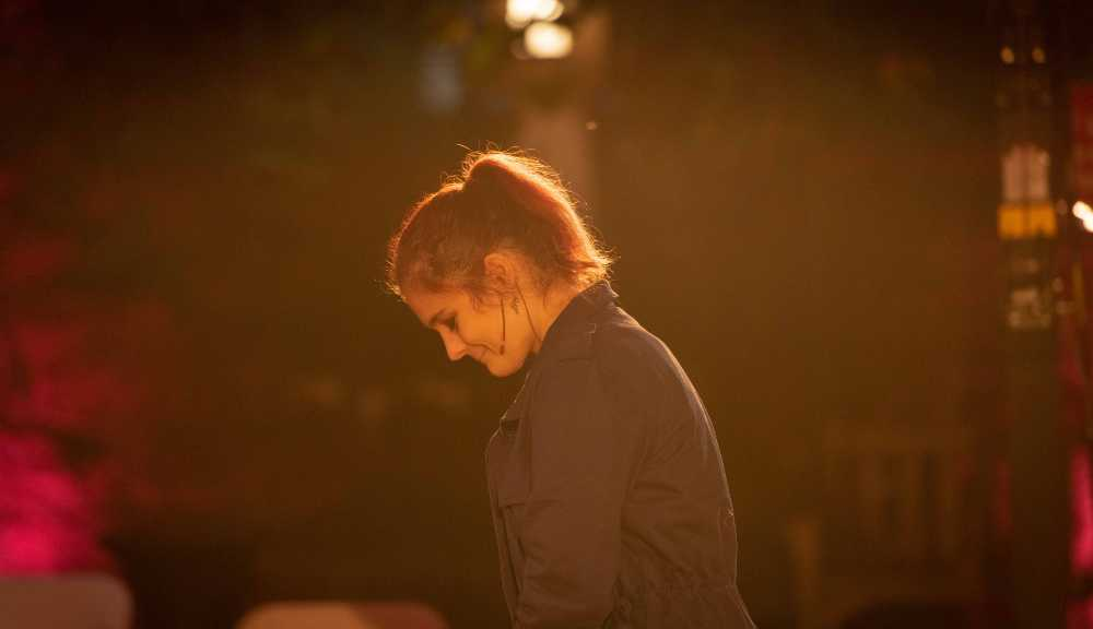 """A side profile of a student bathed in yellow light while performing """"Every Brilliant Thing."""""""
