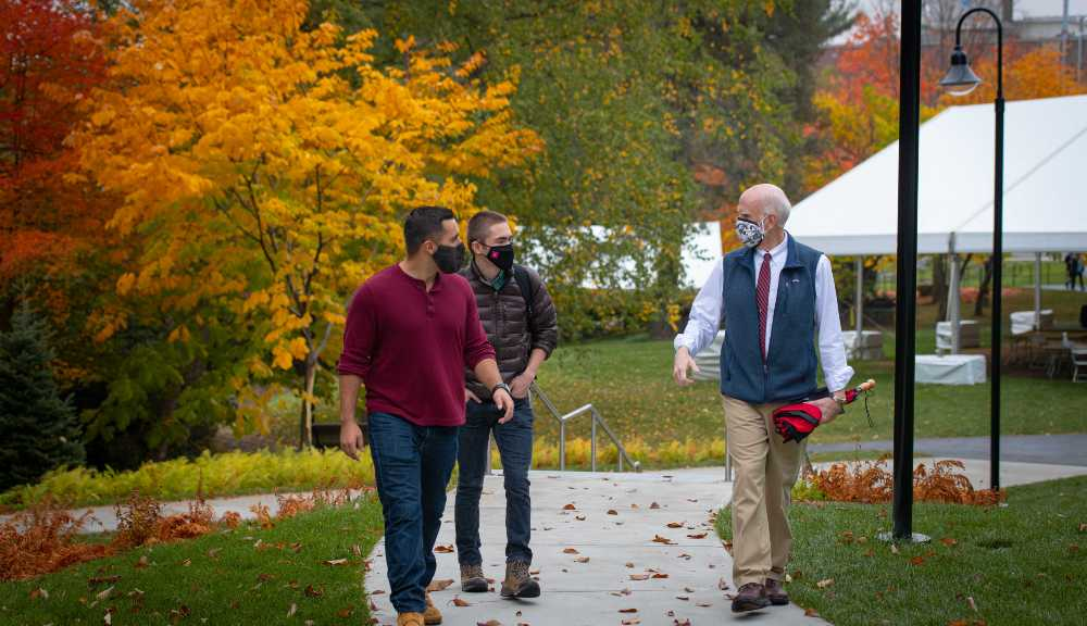 Art Heinricher talks with two students as they walk through campus.